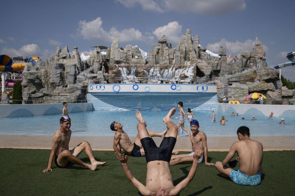 Alcuni ragazzi aggiustano la tintarella tra un bagno e l'altro nell'acquapark Munsu di Pyongyang
