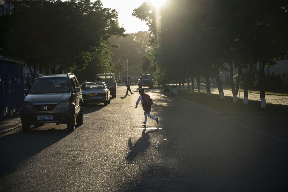 Un bambino gioca tra ombra e sole in una via di Pyongyang