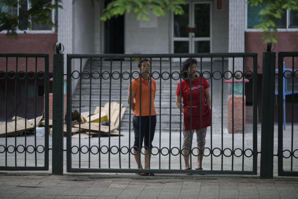 Due donne dietro ad un cancello di una scuola, in una pausa dal lavoro