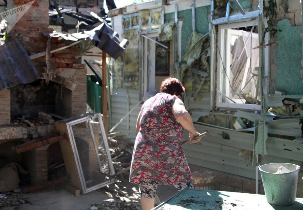 Una donna pulisce la spazzatura nel cortile di un edificio residenziale danneggiato da un bombardamento  a Donetsk.