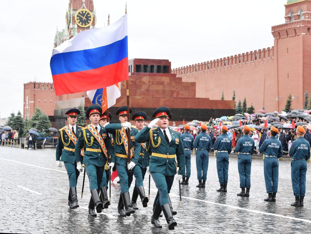 Gli alfieri del Ministero delle Situazioni d'Emergenza della Federazione Russa portano la bandiera del paese sulla Piazza Rossa