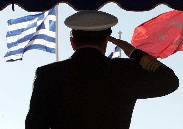 Un militare sullo sfondo delle brandiere della Grecia e della Turchia