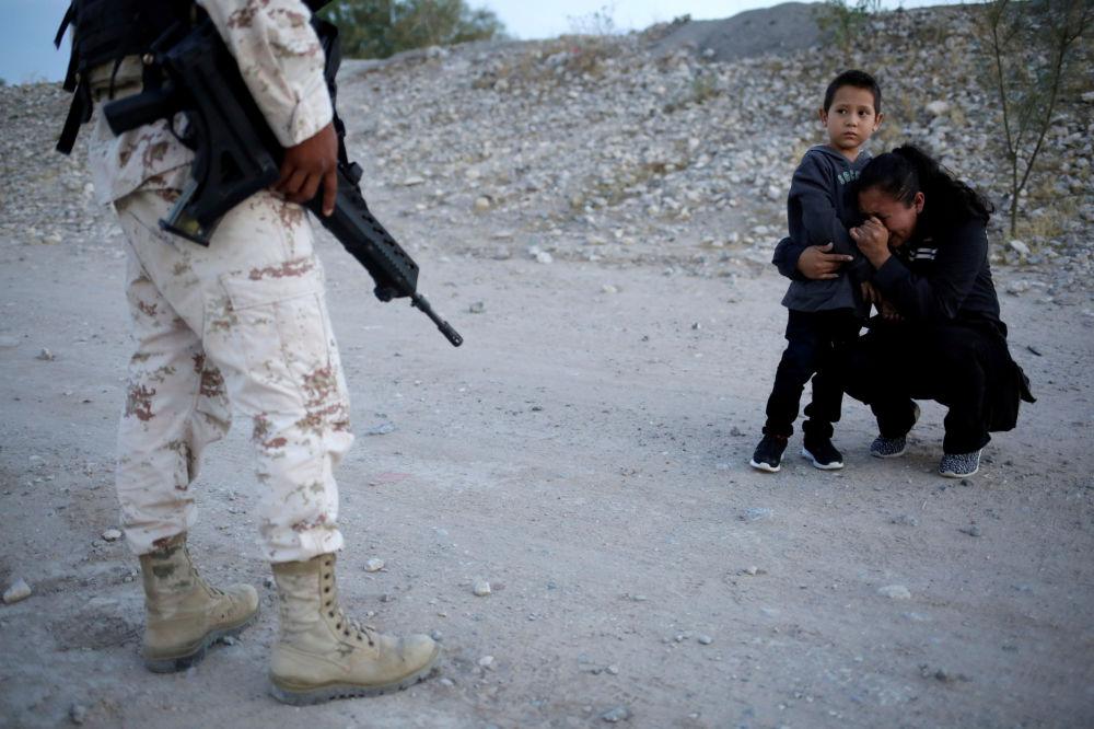 Migrante guatemaliano Lety Perez con il suo figlio supplicano il militare di far passare il confine con gli Usa.