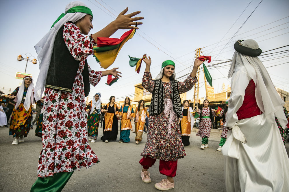I curdi siriani con gli abiti tradizionali Dabke al festival di strada a Rumaylan nella provincia siriana di Hasakeh.