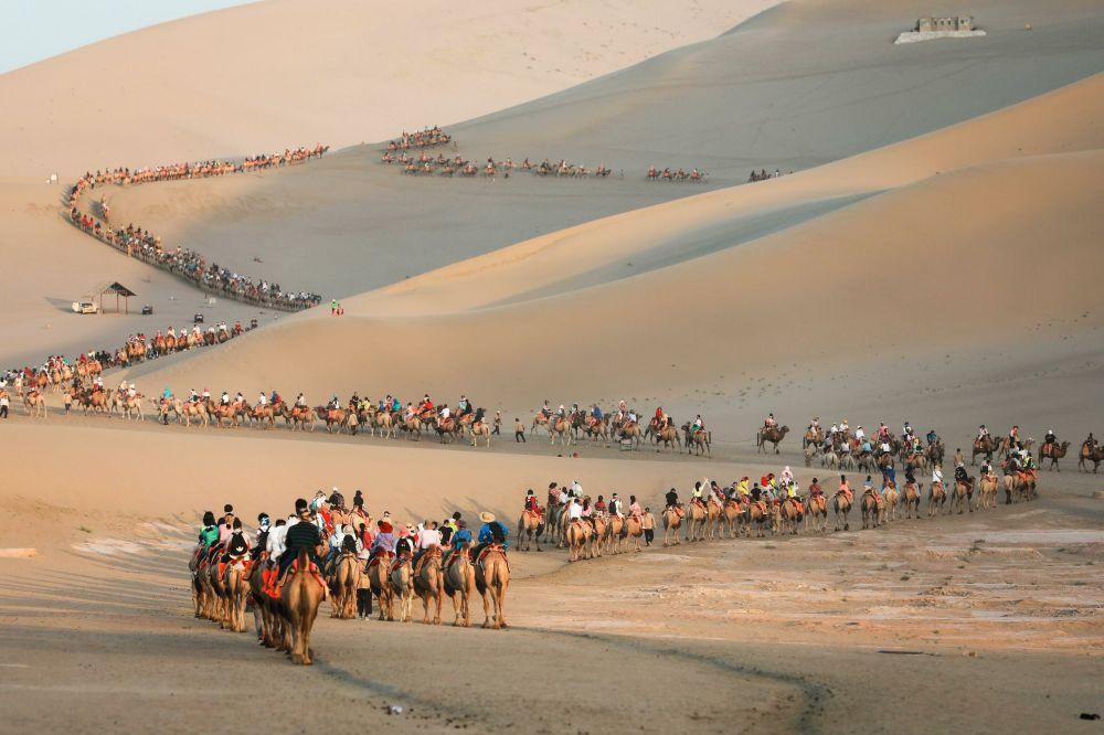 Una carovana di turisti sui cammelli nel deserto del Dunhuang in Cina