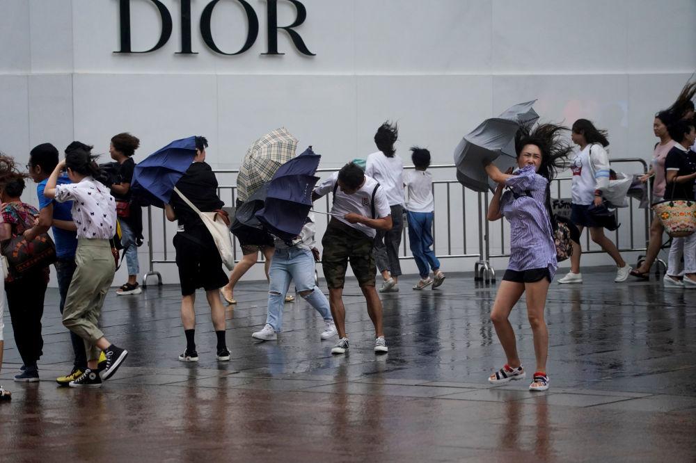 Passanti sorpresi dalle piogge causate dal tifone Lekima a Shangai, in Cina