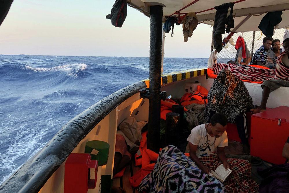 Migranti a bordo della nave Open Arms nel giorno di Ferragosto