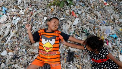 Questi bambini giocano sopra un cumulo di rifiuti
