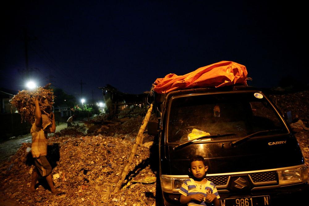 Un bambino aspetta che suo padre carichi la spazzatura sul loro pick-up, prima di portarla alla discarica di Bangun