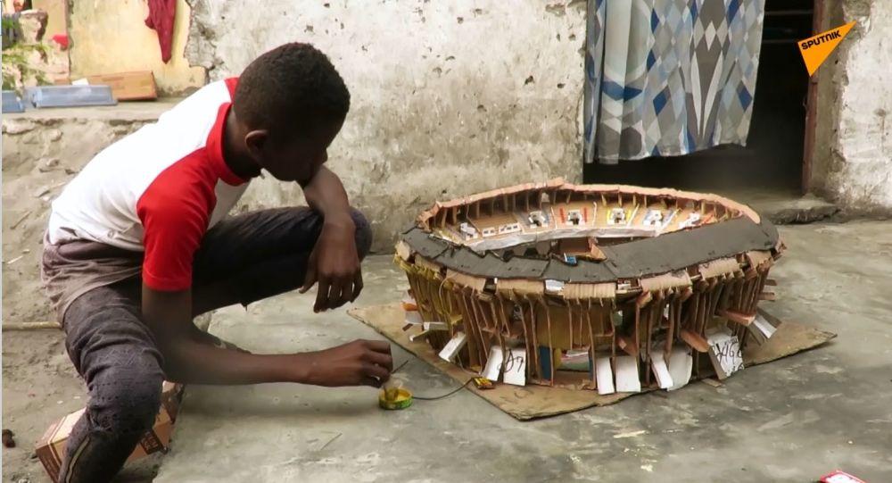 Un ragazzino del Congo costruisce modellini degli stadi
