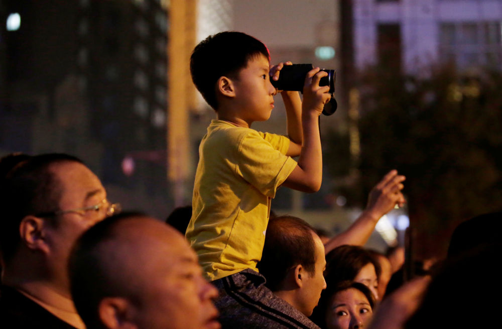 Un ragazzo osserva con il binocolo le prove della Parata.