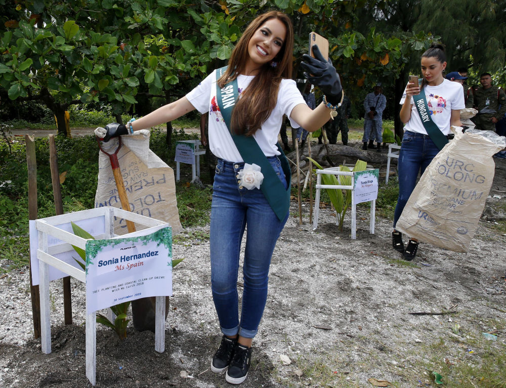 Le candidate di Spagna ed Ungheria per il concorso Miss Earth 2019 si fanno delle foto prima della pulizia della spiaggia.