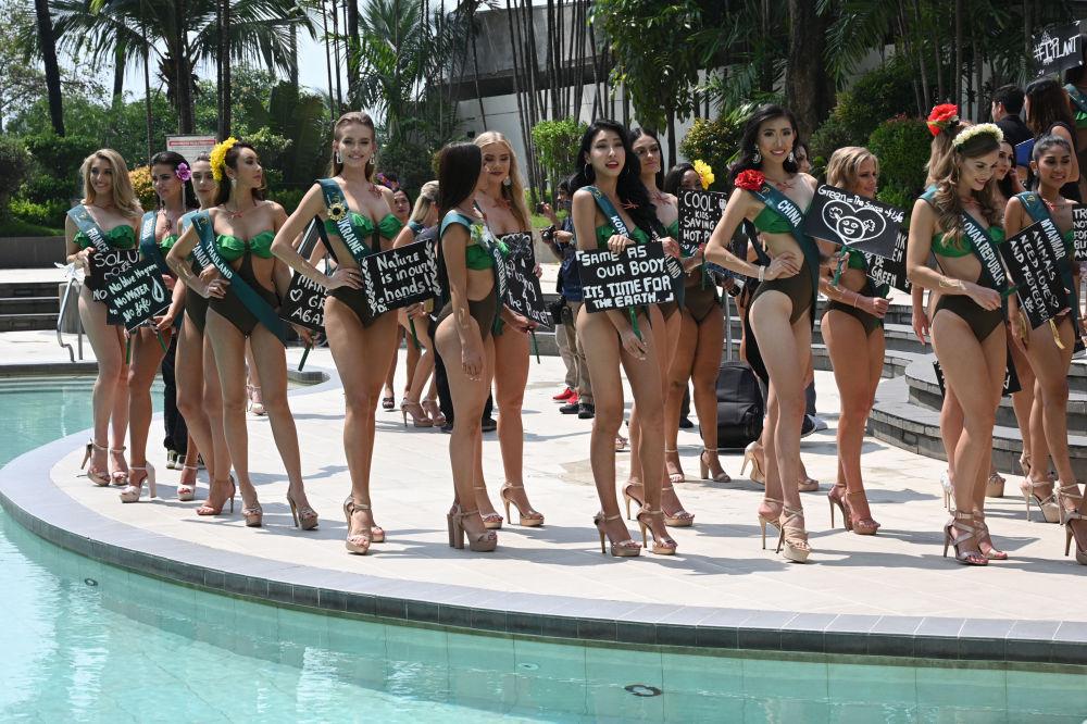 Le candidate alla Miss Earth 2019 con poster con slogan ambientali a Manila.