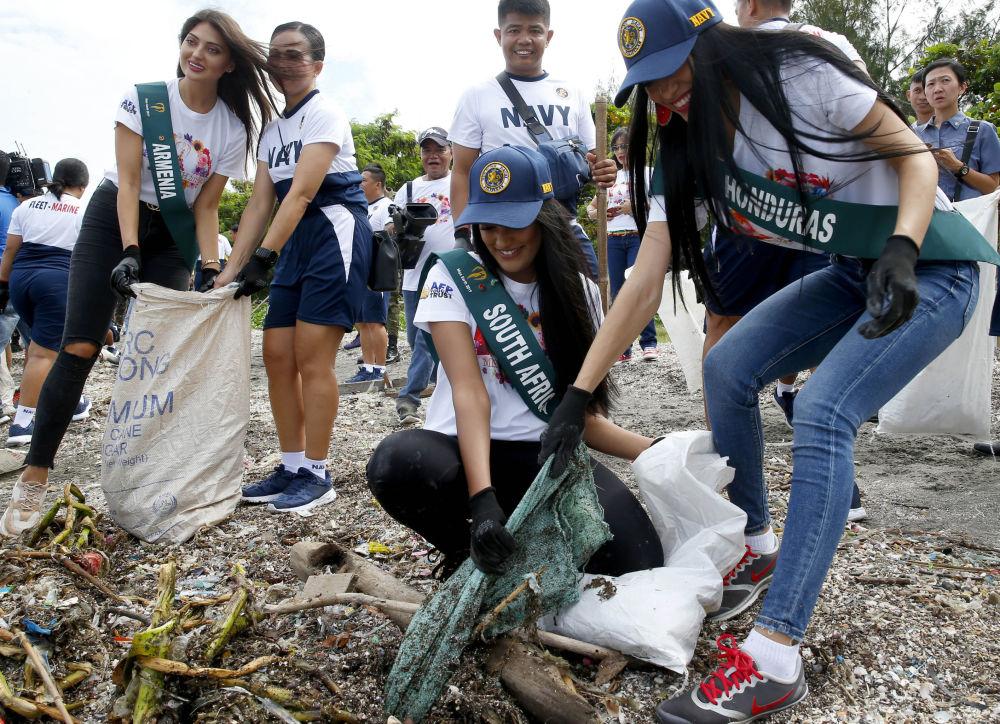 Le candidate in corsa per il titolo di Miss Earth durante la pulizia costiera.