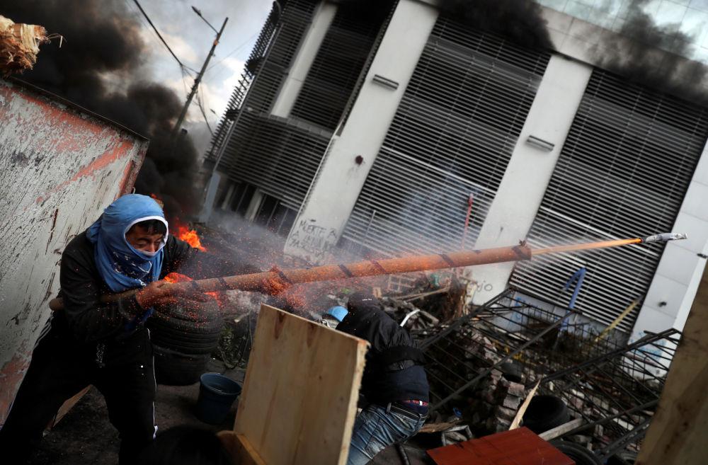 Un manifestante spara un colpo da un'arma rudimentale durante le proteste a Quito, in Ecuador.