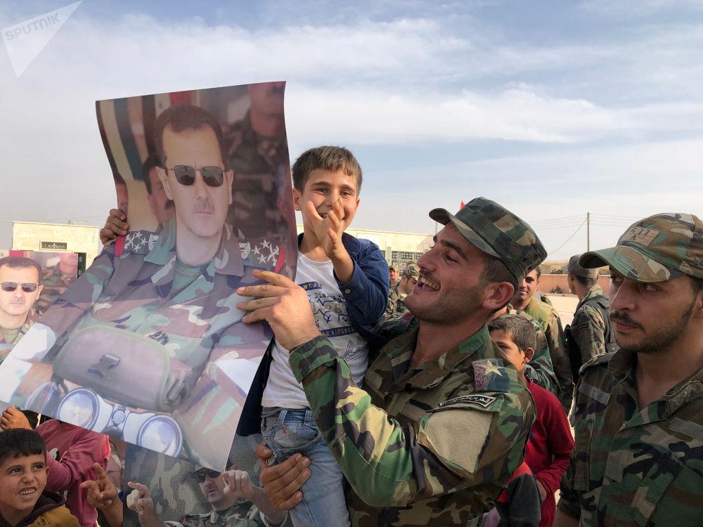 I militari siriani festeggiano dopo aver conquistato la città di Manbij.