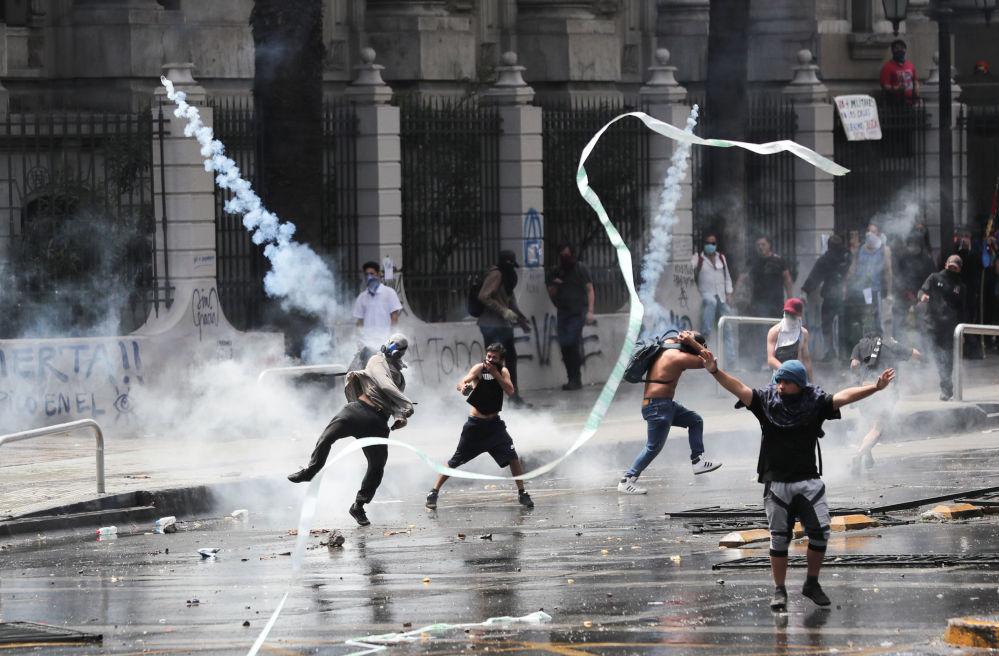 Un manifestante lancia una bomboletta di gas lacrimogeni durante le proteste in Piazza Italia a Santiago il 23 ottobre 2019, Cile
