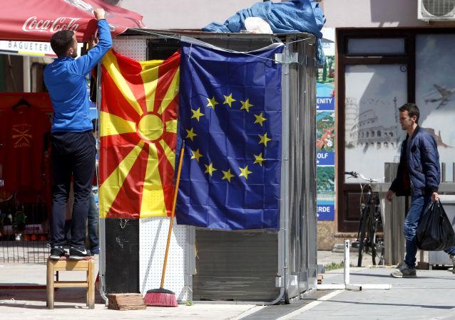 Un venditore affigge la bandiera macedone accanto a quella europea in una strada di Skopje