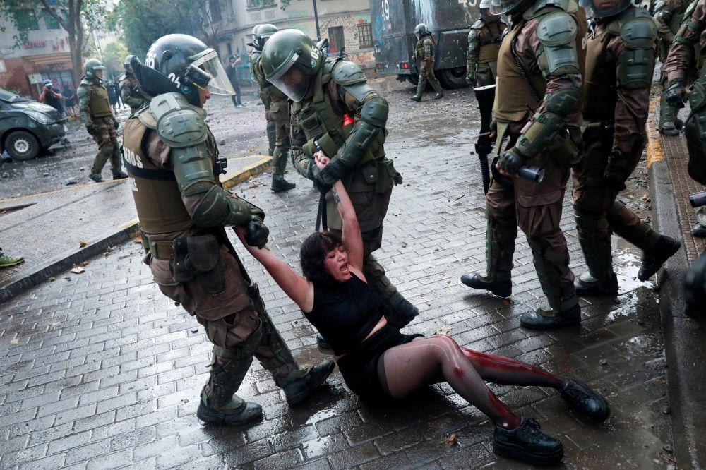 Una manifestante ferita viene arrestata delle forze di sicurezza durante una protesta contro il governo cileno a Santiago