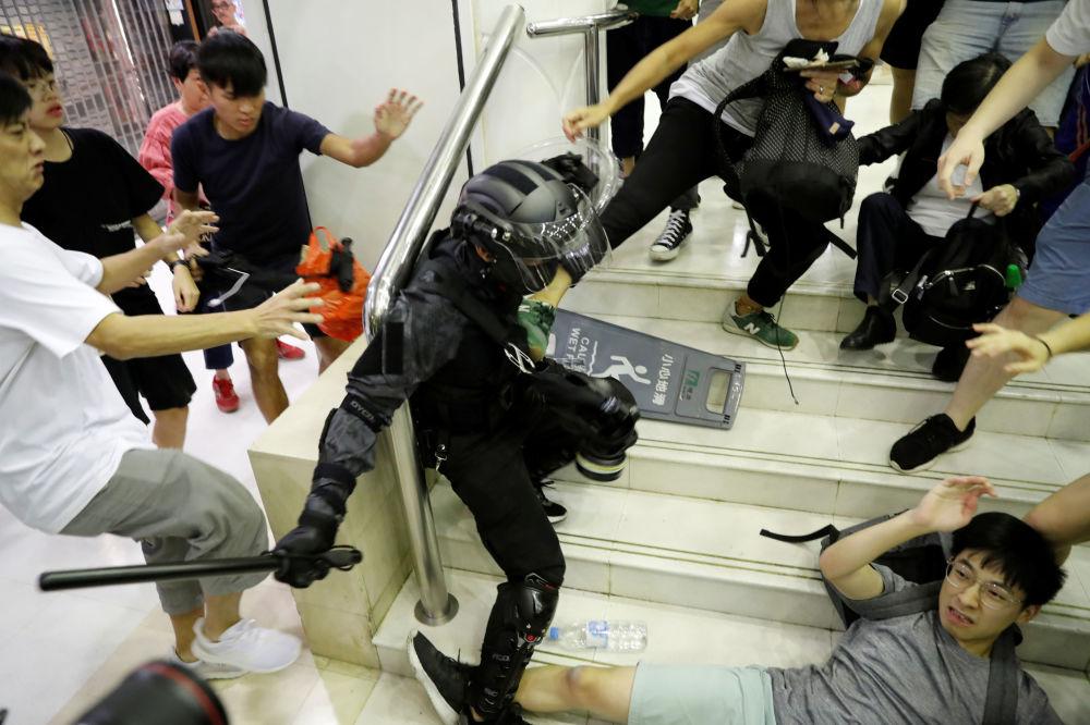 La gente si scontra con un poliziotto in un centro commerciale nel Tai Po di Hong Kong, Cina