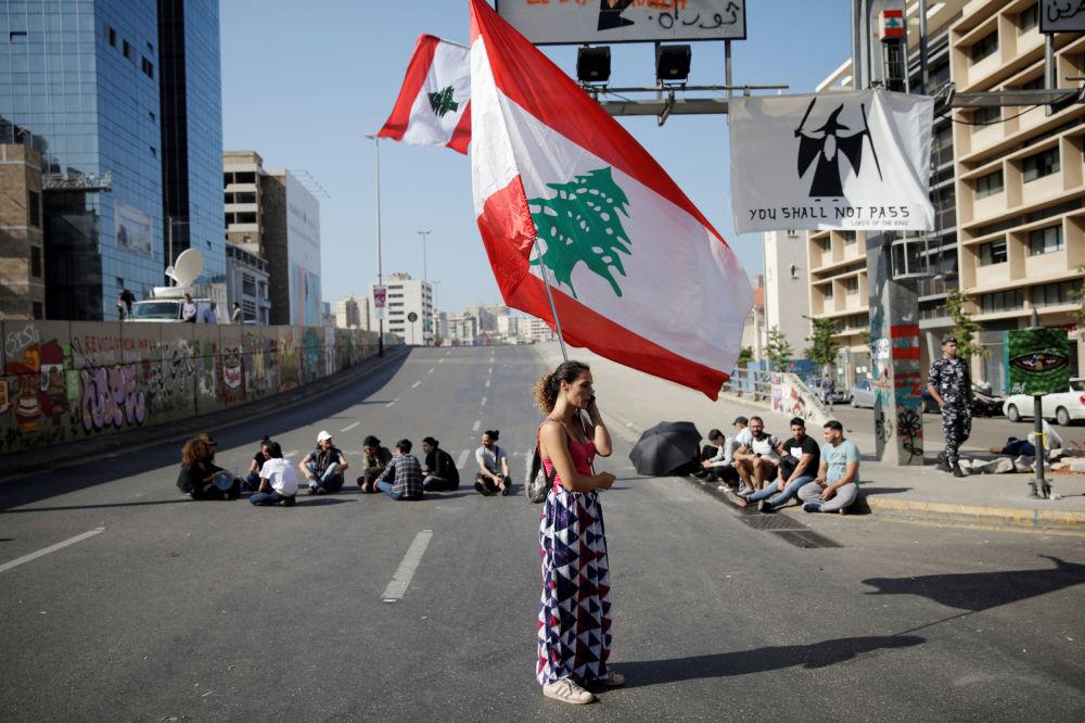 Una donna con la bandiera libanese durante le proteste antigovernative a Beirut