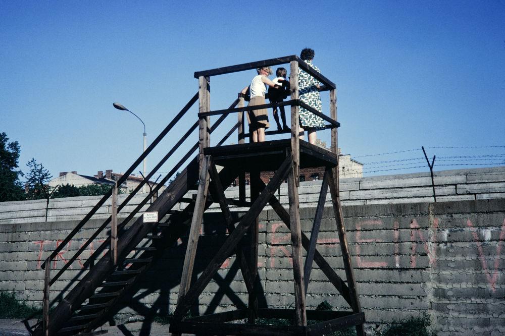 La gente osserva da una torre ciò che accade  dietro il muro a Berlino Ovest, giugno 1968