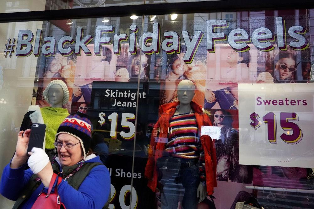 Una signora si fa un selfie vicino a un negozio con la pubblicità del Black Friday a New York, USA