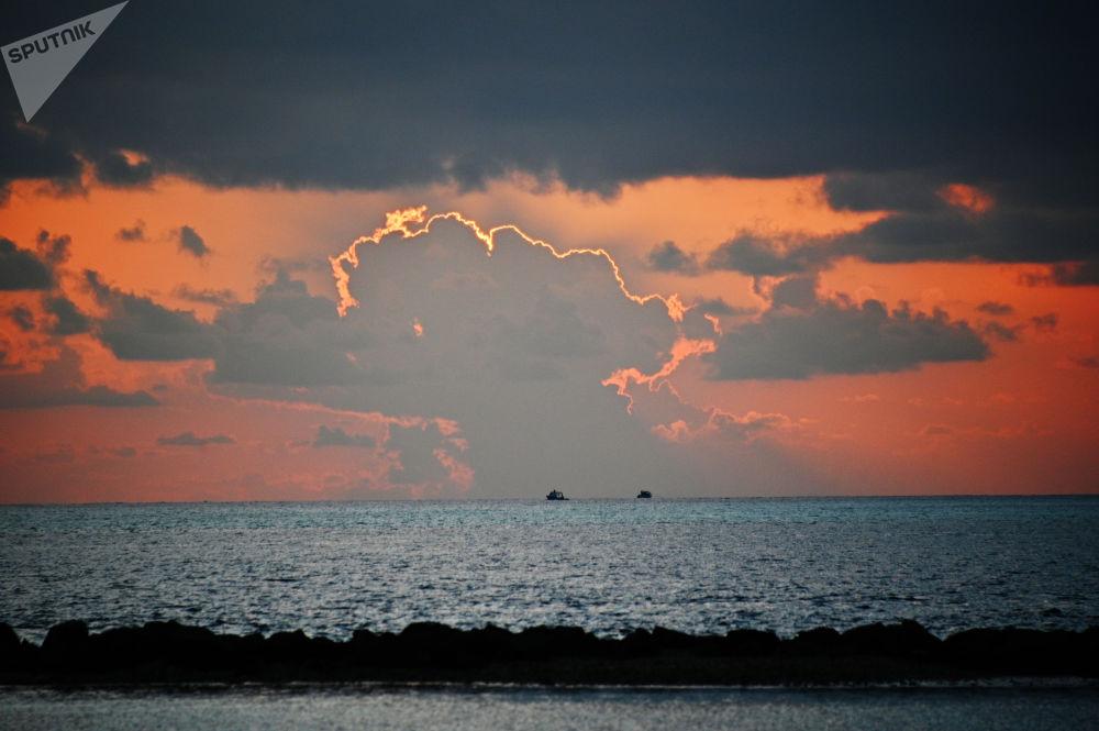 La vista del mare da un'isola delle Maldive al tramonto.