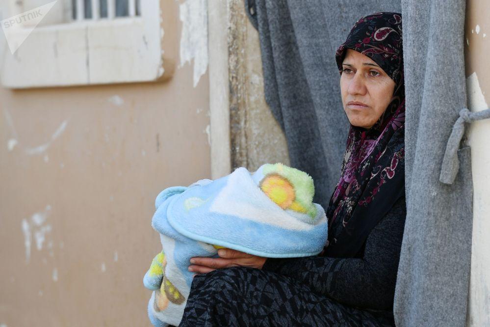 Una donna con un bambino nel campo profughi di Kharzholi vicino a Damasco