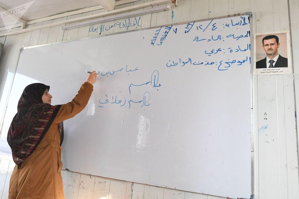 Un insegnante a scuola nel campo profughi di Kharzholi vicino a Damasco