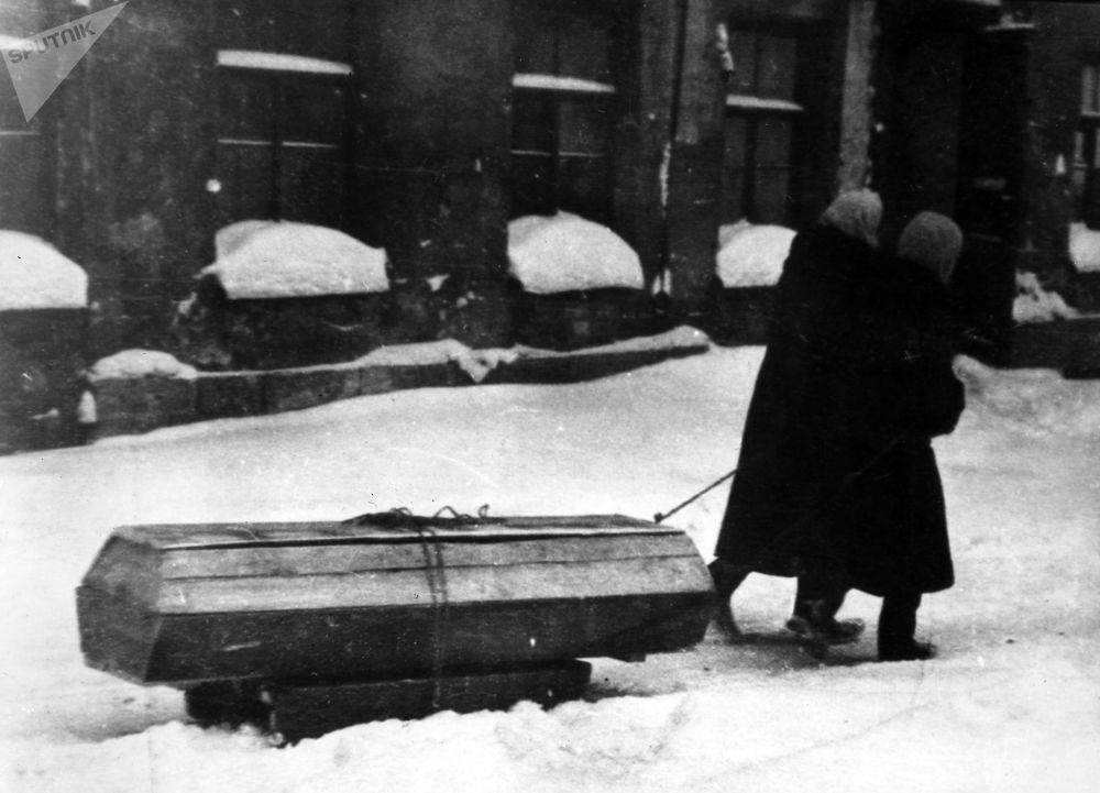 I residenti della città portano su una slitta una bara con un defunto durante l'assedio di Leningrado, 1941-1944