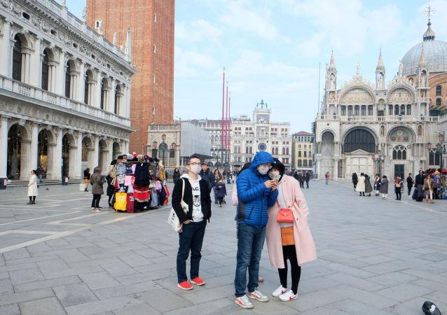 Turisti in maschere sulla piazza San Marco a Venezia