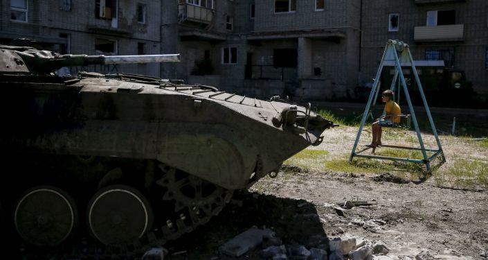 Un bambino seduto su un'altalena di fronte a un tank dell'esercito
