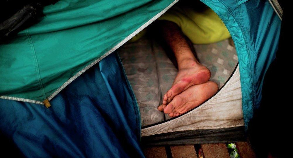 Un migrante dorme in una tenda vicino a Calais, Francia.
