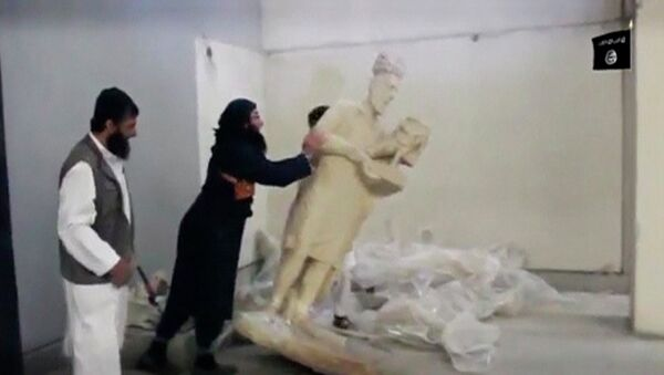 A man topples a statue in a museum at a location said to be Mosul in this still image taken from an undated video published by Islamic State on February 26, 2015 - Sputnik Italia