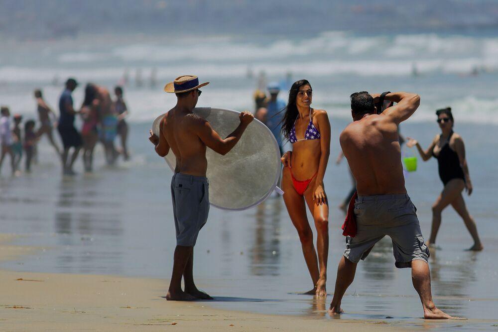 Una ragazza si fa fotografare da un fotografo in una spiaggia a San Diego, USA.