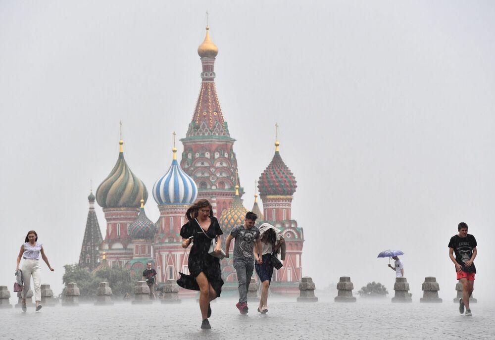 La gente corre nella Piazza Rossa durante un acquazzone a Mosca.