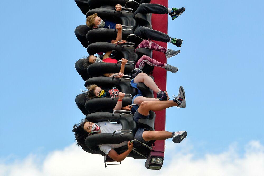 La gente in mascherina si diverte su un'attrazione nel parco divertimenti Thorpe Park, Gran Bretagna.
