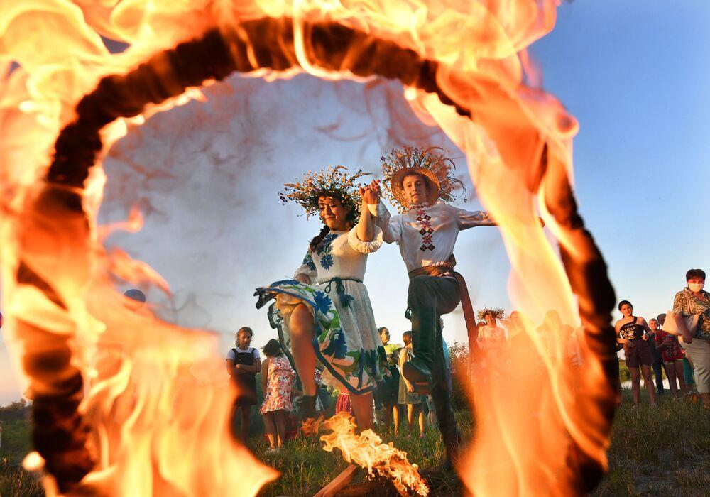 Una ragazza e un ragazzo saltano nell fuoco alla festa di Ivan Kupala sulla riva della baia di Pripyat nell'antica città bielorussa di Turov.