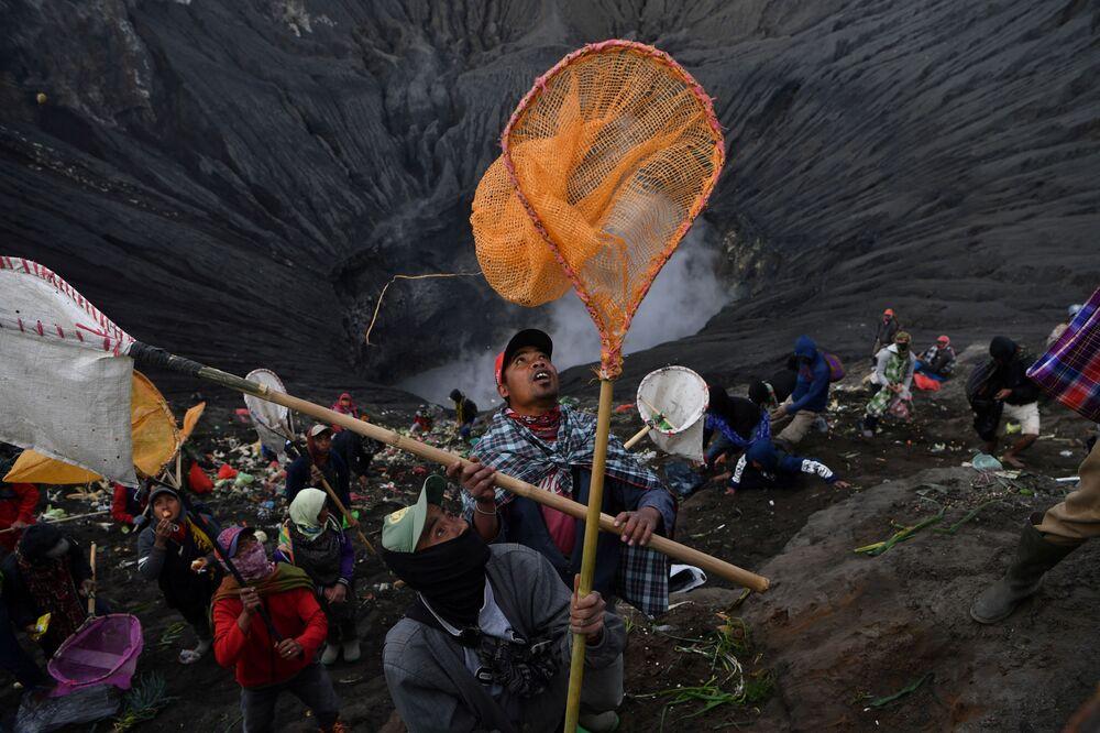 Gli abitanti rurali colgono con gli acchiappafarfalle le monete, gettate nel cratere durante una cerimonia induistica.