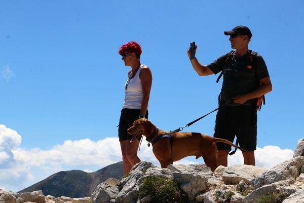 Un uomo ed una donna con un cane in montagna - Sputnik Italia