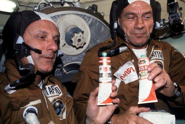 Gli astronauti Thomas P. Stafford (a sinistra) e Donald K. Deke Slayton con i contenitori di cibo spaziale sovietico nel veicolo spaziale Soyuz dopo l'attracco delle navicelle spaziali. I contenitori contengono il borsch (zuppa di barbabietola) sui quali sono state incollate le etichette di vodka. - Sputnik Italia