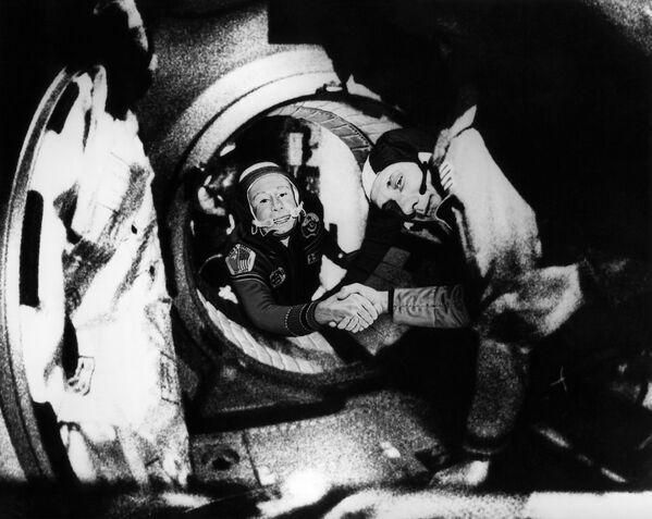 Il comandante dell'equipaggio sovietico di Soyuz, Alexey Leonov e il comandante dell'equipaggio americano di Apollo, Thomas Stafford, si stringono le mani nello spazio, da qualche parte sopra la Germania occidentale, dopo le manovre di attracco Apollo-Soyuz - Sputnik Italia