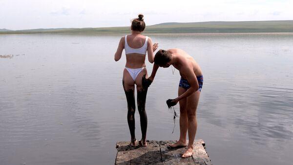 Un uomo spalma su una ragazza fango di solfuro del lago Tus nella Repubblica di Khakassia, Russia. - Sputnik Italia