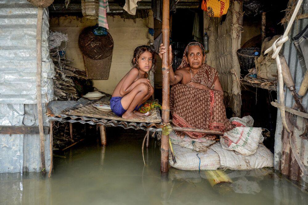 Una ragazza e una donna nella casa allagata a Sunamganj, Bangladesh.