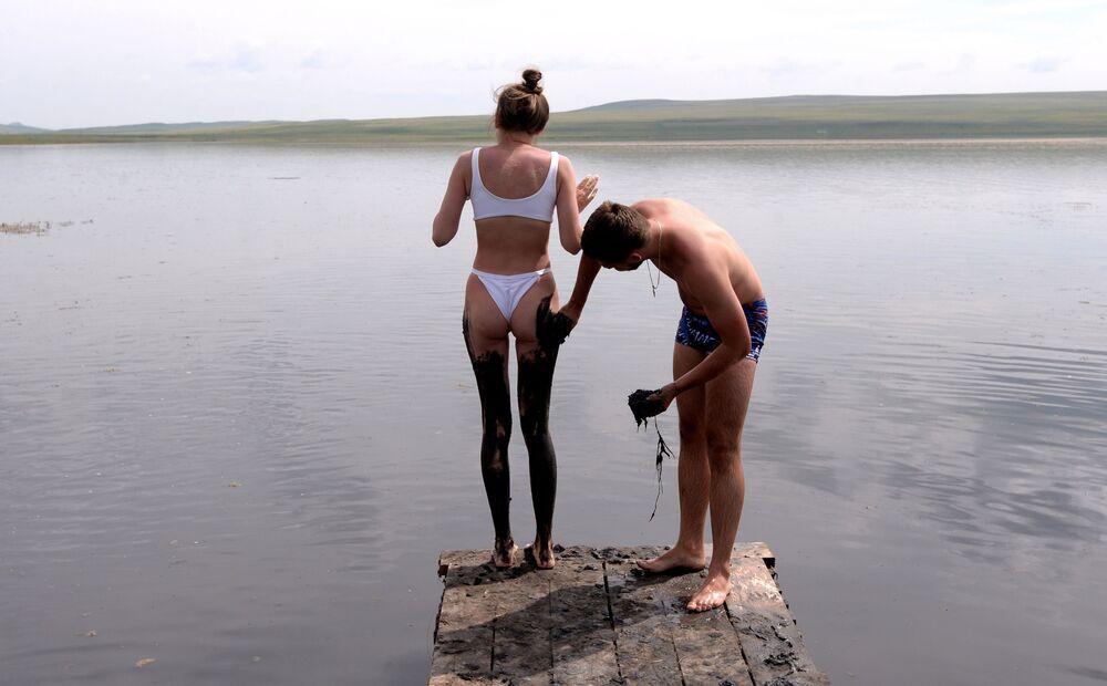 Un uomo spalma una ragazza con fango di solfuro del lago Tus nella Repubblica di Khakassia, Russia.