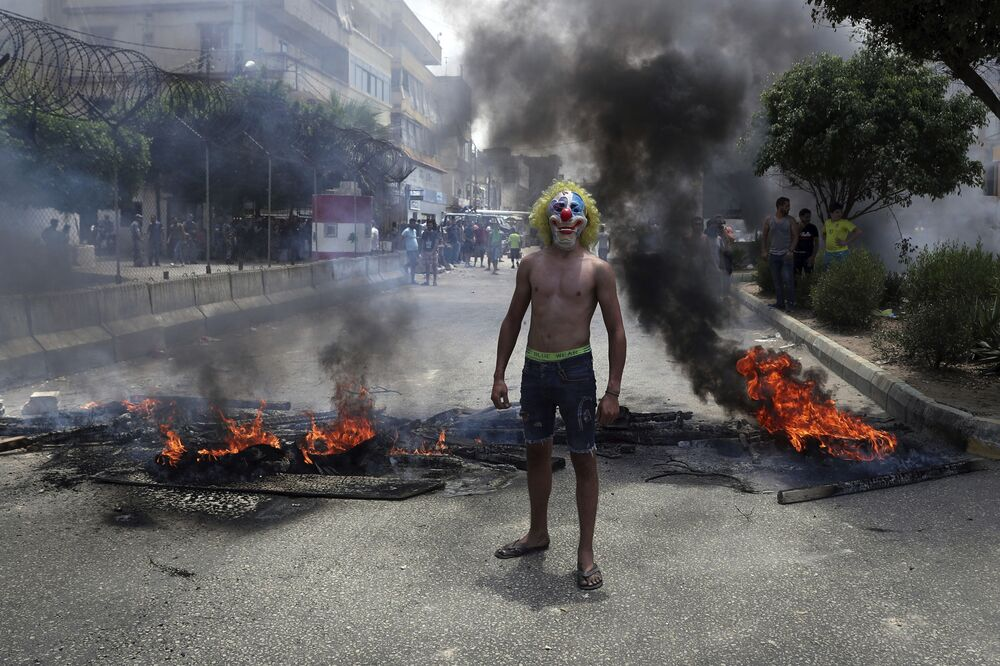 Un uomo in maschera da pagliaccio prende parte alle proteste antigovernative a Beirut, Libano.