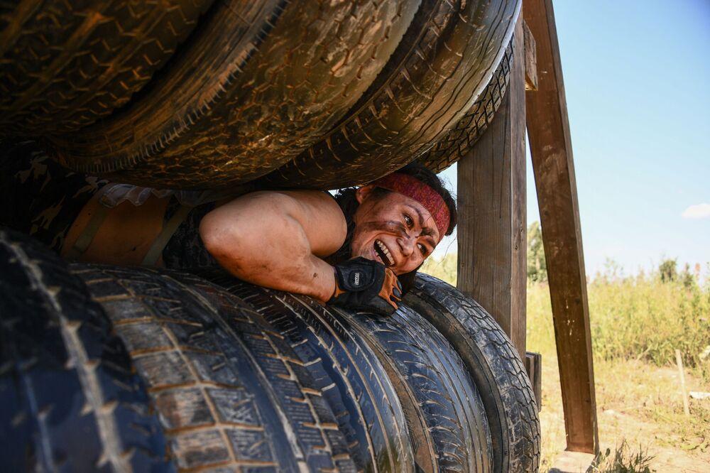 Una partecipante al gioco sportivo La corsa degli eroi passa la zona degli ostacoli in Russia.