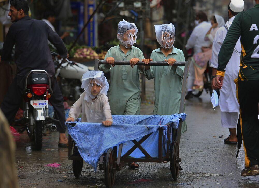 Degli adolescenti durante la pioggia a Pashawar, Pakistan.