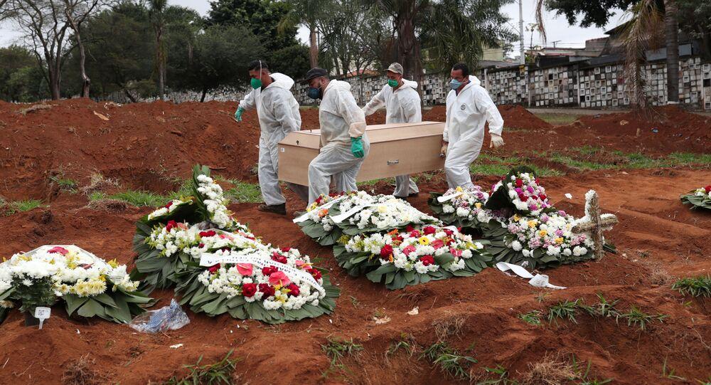 Becchini con tuta protettiva trasportano la bara di una donna di 63 anni deceduta per il COVID-19, al cimitero Vila Formosa, in Sao Paulo, Brasile, 26 giugno 2020. REUTERS/Amanda Perobelli